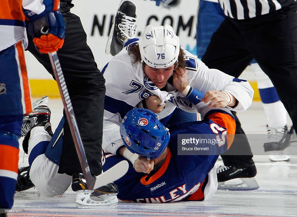 Joe Finley #52 of the New York Islanders fights with Pierre-Cedric Labrie #76 of the Tampa Bay Lightning one second into the game at the Nassau Veterans Memorial Coliseum on January 21, 2013 in Uniondale, New York.