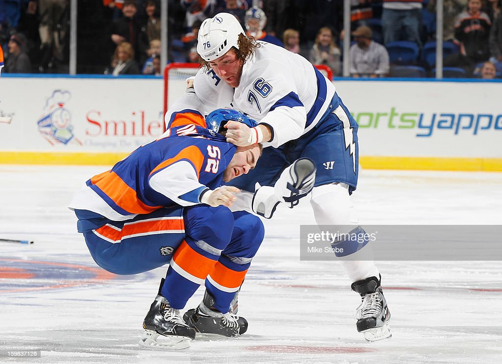 Joe Finley #52 of the New York Islanders gets tangled up with Pierre-Cedric Labrie #76 of the Tampa Bay Lightning at Nassau Veterans Memorial Coliseum on January 21, 2013 in Uniondale, New York.