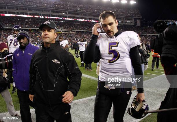 Joe Flacco of the Baltimore Ravens and head coach John Harbaugh walk off the field after losing to the New England Patriots in the AFC Championship...