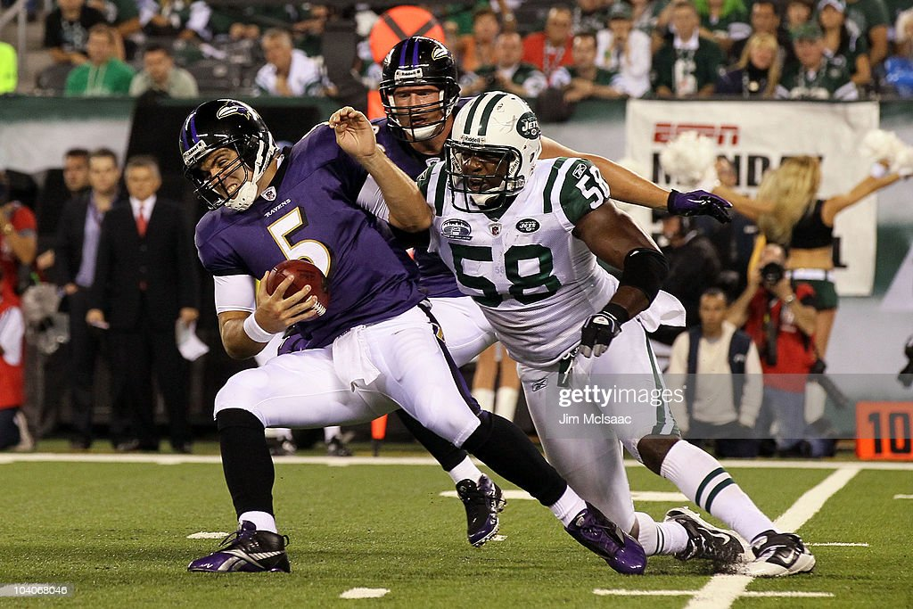 Joe Flacco of the Baltimore Ravens gets sacked by Bryan Thomas of the New York Jets during their home opener at the New Meadowlands Stadium on...