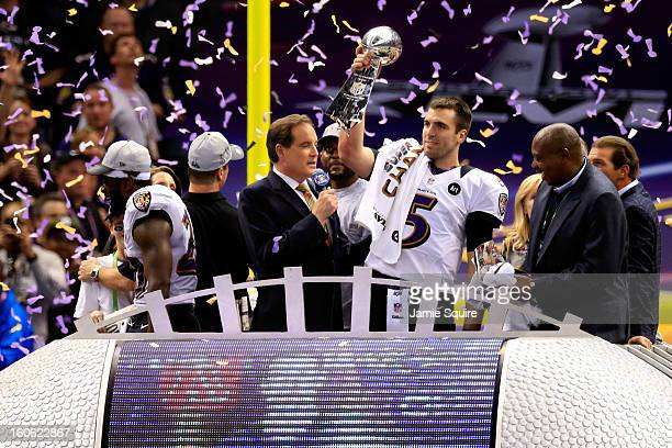 Joe Flacco of the Baltimore Ravens holds up the Vince Lombardi Trophy in front of CBS host Jim Nantz following their 3431 win against the Baltimore...