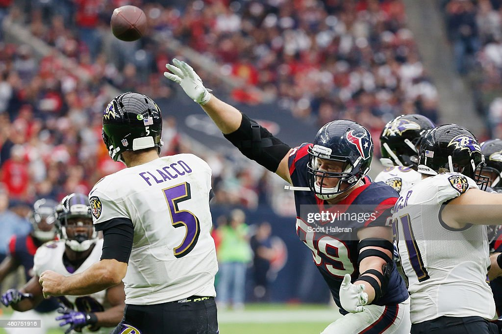 Joe Flacco #5 of the Baltimore Ravens is pressured by J.J. Watt #99 of the Houston Texans during their game at NRG Stadium on December 21, 2014 in Houston, Texas.