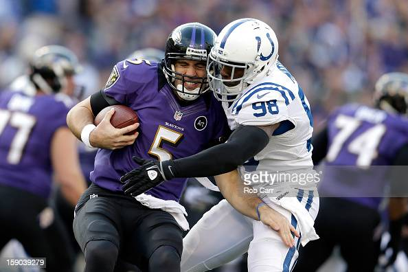 Joe Flacco of the Baltimore Ravens is sacked by Robert Mathis of the Indianapolis Colts in the third quarter during the AFC Wild Card Playoff Game at...