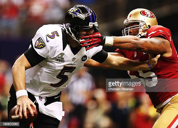 Joe Flacco of the Baltimore Ravens runs with the ball against Ahmad Brooks of the San Francisco 49ers during Super Bowl XLVII at the MercedesBenz...