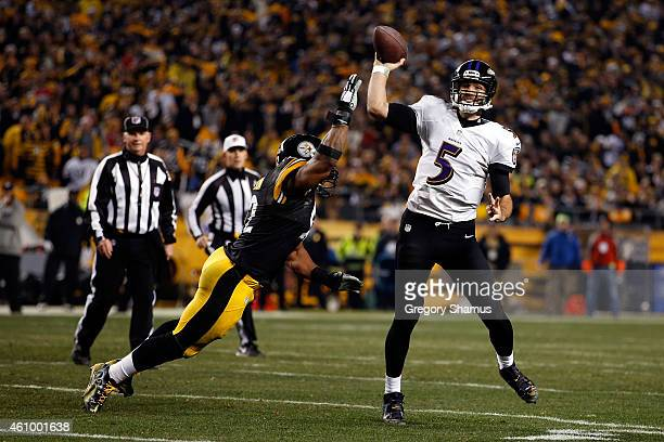 Joe Flacco of the Baltimore Ravens throws under pressure from James Harrison of the Pittsburgh Steelers during their AFC Wild Card game at Heinz...