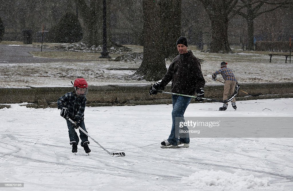 Joe Flaherty, center, and his son Liam, 9, left, play ice hockey on Duck Pond in Boston, Massachusetts, U.S., on Friday, Feb. 8, 2013. The New England cities are expected to receive more than 2 feet of snow by the time Winter Storm Nemo moves out tomorrow night, according to the weather service. Photographer: Kelvin Ma/Bloomberg via Getty Images