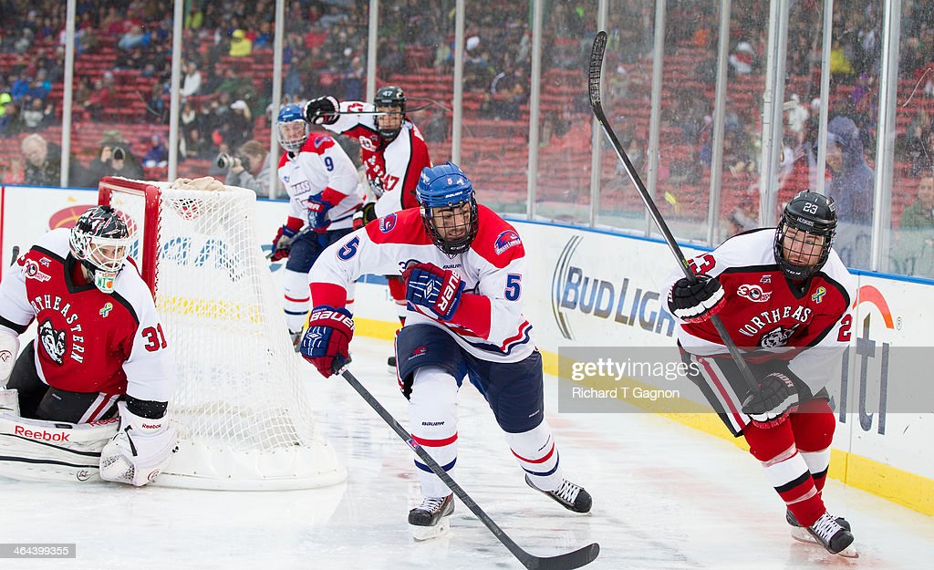 Joe Gambardella #5 of the Massachusetts Lowell River Hawks skates against the Northeastern University Huskies Colton Saucerman #23 and Clay Witt #31 during NCAA hockey action in the 'Citi Frozen Fenway 2014' at Fenway Park on January 11, 2014 in Boston, Massachusetts.