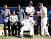 Joe Girardi of the New York Yankees and Derek Jeter present Mariano Rivera with a rocking chair made of baseball bats during the Mariano Rivera Day...