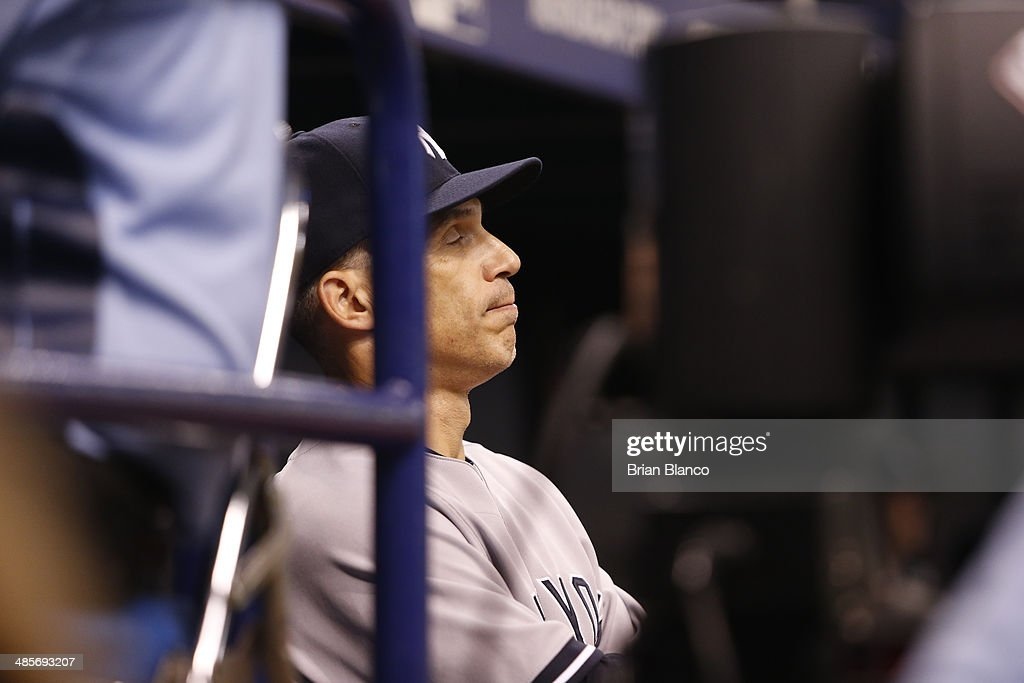 Joe Girardi #28 of the New York Yankees looks on from the dugout as shortstop Dean Anna of the New York Yankees takes over pitching duties during the eighth inning of a game against the Tampa Bay Rays on April 19, 2014 at Tropicana Field in St. Petersburg, Florida.