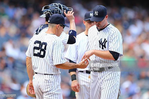 Joe Girardi of the New York Yankees takes out Boone Logan in the seventh inning against the Tampa Bay Rays during their game on June 23 2013 at...