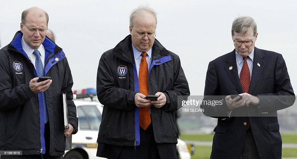 Joe Hagen, White House Deputy Chief of Staff; Karl Rove, Political Advisor to the President; and Steve Hadley, Deputy National Security Advisor all focus on their 'Blackberries' during a campaign stop for US President George W. Bush 27 October, 2004, in Lancaster County, Pennsylvania.