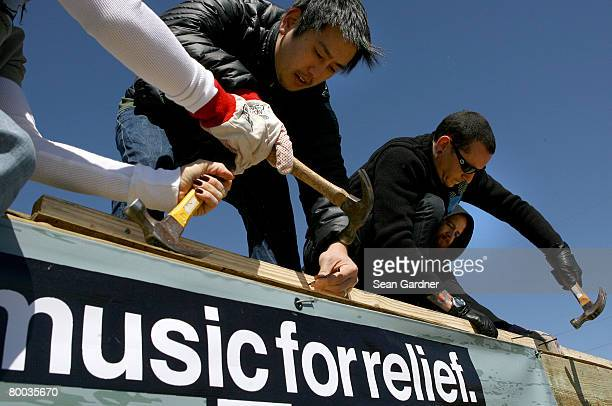 Joe Hahn and Chester Bennington of the band Linkin Park use hammers to nail frames together as they work with Music for Relief and Habitat for...
