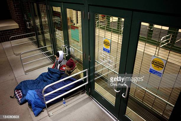 Joe Hallock and Aaron Green wait outside Scheels All Sports in thermal sleeping bags hours before the store opens at 7am on November 25 2011 in Fargo...