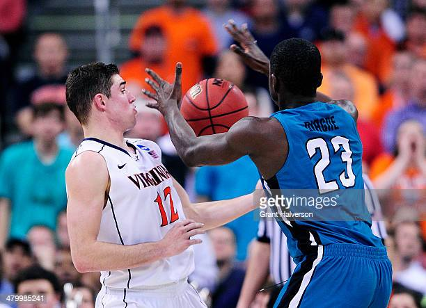 Joe Harris of the Virginia Cavaliers fouls Badou Diagne of the Coastal Carolina Chanticleers in the first half during the Second Round of the 2014...