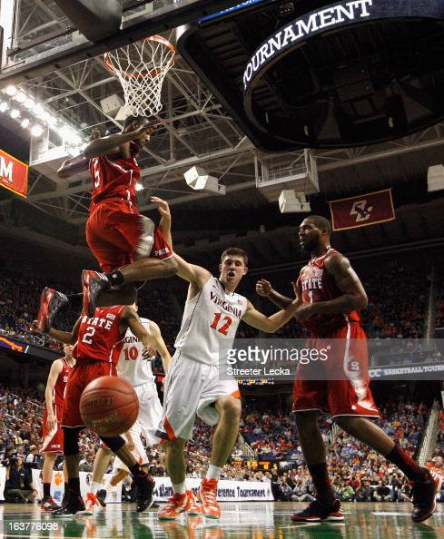 Joe Harris of the Virginia Cavaliers tries to get to a loose ball between teammates CJ Leslie and Richard Howell of the North Carolina State Wolfpack...