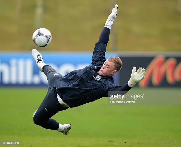 Joe Hart of England dives to save a ball during a training session at St Georges Park on March 19 2013 in BurtonuponTrent England
