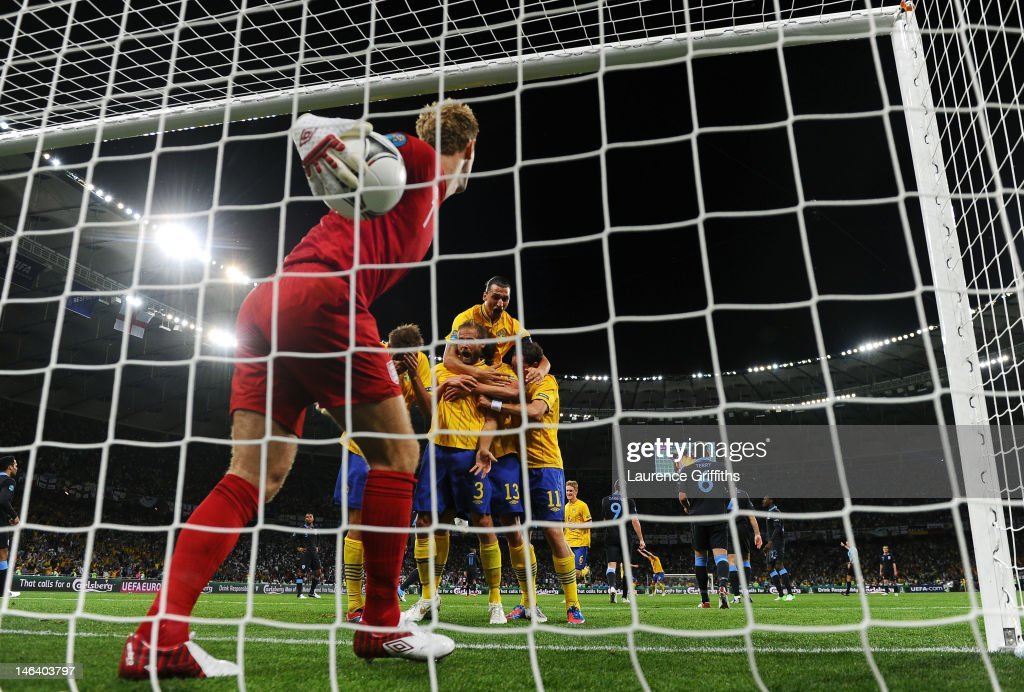 <a gi-track='captionPersonalityLinkClicked' href=/galleries/search?phrase=Joe+Hart&family=editorial&specificpeople=1295472 ng-click='$event.stopPropagation()'>Joe Hart</a> of England pick the ball out of the net as <a gi-track='captionPersonalityLinkClicked' href=/galleries/search?phrase=Olof+Mellberg&family=editorial&specificpeople=215028 ng-click='$event.stopPropagation()'>Olof Mellberg</a> of Sweden celebrates scoring their second goal with team mates during the UEFA EURO 2012 group D match between Sweden and England at The Olympic Stadium on June 15, 2012 in Kiev, Ukraine.