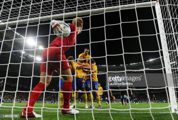 Joe Hart of England pick the ball out of the net as Olof Mellberg of Sweden celebrates scoring their second goal with team mates during the UEFA EURO...
