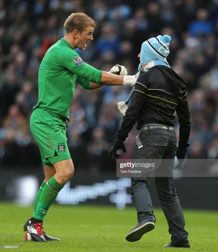 <a gi-track='captionPersonalityLinkClicked' href=/galleries/search?phrase=Joe+Hart&family=editorial&specificpeople=1295472 ng-click='$event.stopPropagation()'>Joe Hart</a> of Manchester City apprehends a pitch invader during the Barclays Premier League match between Manchester City and Manchester United at Etihad Stadium on December 9, 2012 in Manchester, England.
