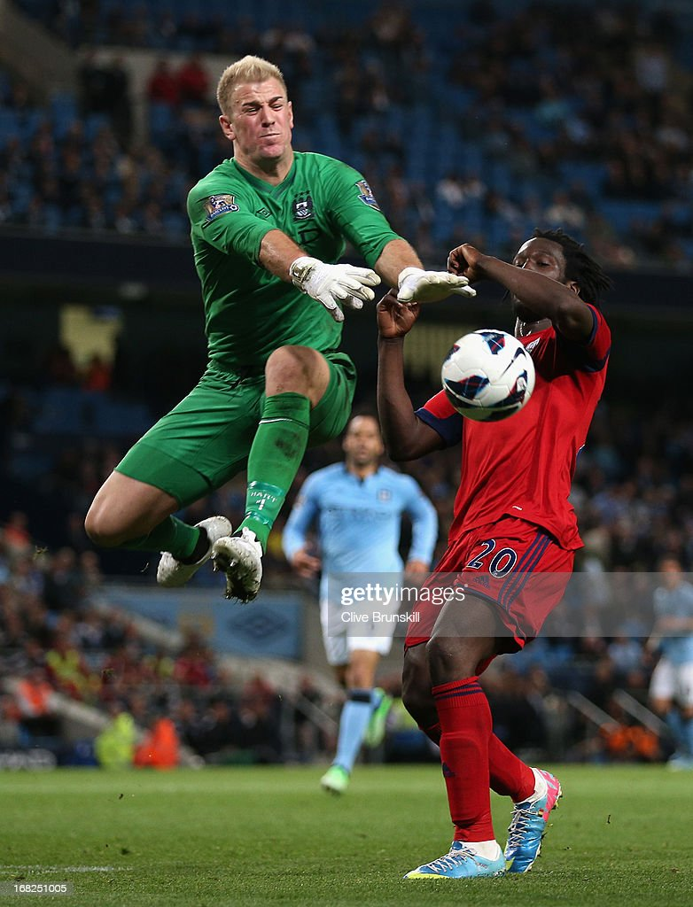Joe Hart of Manchester City blocks the attempt on goal of Youssouf Mulumbu of West Bromwich Albion during the Barclays Premier League match between Manchester City and West Bromwich Albion at the Etihad Stadium on May 07, 2013 in Manchester, England.