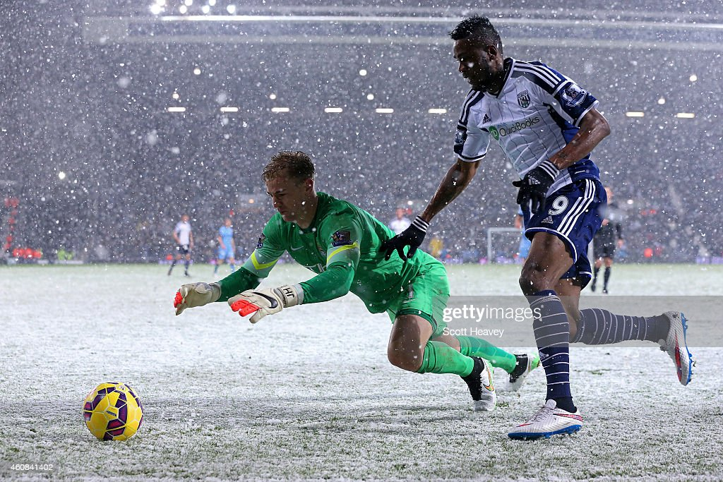 Joe Hart of Manchester City dives for the ball under pressure from Brown Ideye of West Brom during the Barclays Premier League match between West Bromwich Albion and Manchester City at The Hawthorns on December 26, 2014 in West Bromwich, England.