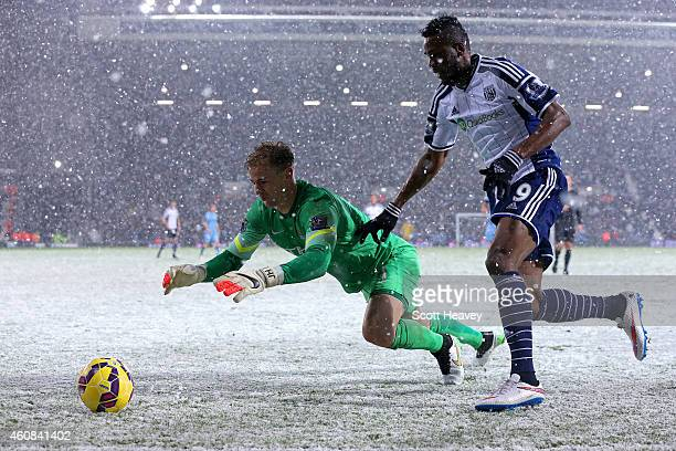 Joe Hart of Manchester City dives for the ball under pressure from Brown Ideye of West Brom during the Barclays Premier League match between West...