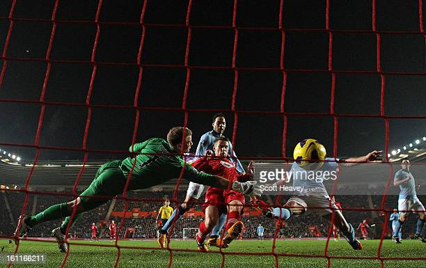 Joe Hart of Manchester City dives in vain as Steven Davis of Southampton scores their second goal during the Barclays Premier League match between...
