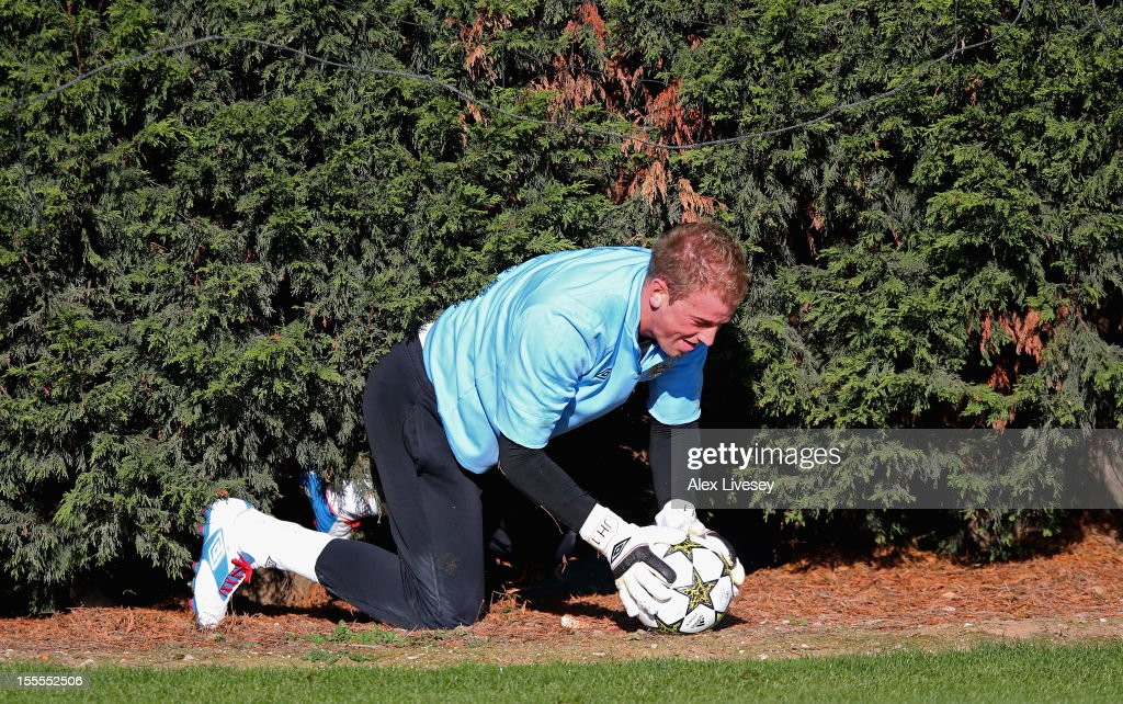 Joe Hart of Manchester City retrieves a ball from under a hedge during a training session at the Carrington Training Ground on November 5, 2012 in Manchester, England.