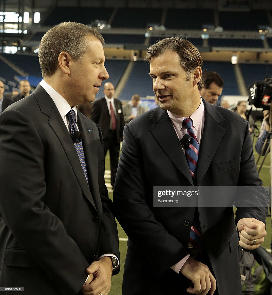 Joe Hinrichs, president of the Americas for Ford Motor Co., left, speaks with Jim Farley, group vice president of global marketing, sales and service for Ford Motor Co., during an event at Ford Field in Detroit, Michigan, U.S., on Friday, Dec. 14, 2012. Ford Motor Co. is talking to the U.S. Environmental Protection Agency about how it tests fuel economy performance on new vehicles following reports that the automaker's hybrids are falling short of mileage promises. Photographer: Jeff Kowalsky/Bloomberg via Getty Images