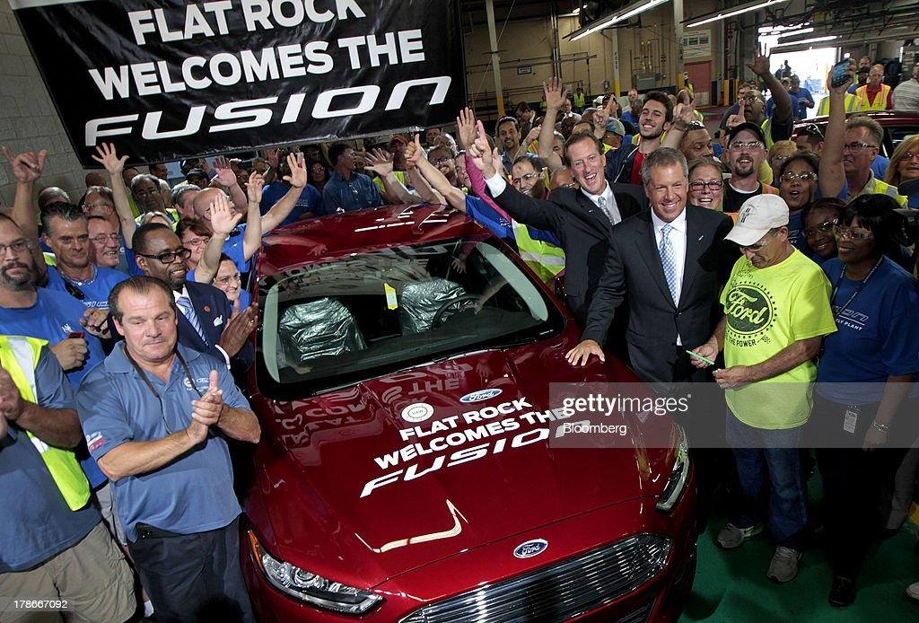 Joe Hinrichs, president of the Americas for Ford Motor Co., third right, stands with employees as they cheer during an event at the Ford Motor Co. Flat Rock Assembly Plant in Flat Rock, Michigan, U.S., on Thursday, Aug.. 29, 2013. Ford will add a shift of 1,400 new workers at the Flat Rock plant to boost Fusion capacity more than 30 percent, according to a statement from the company. Photographer: Jeff Kowalsky/Bloomberg via Getty Images