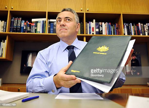 Joe Hockey Australia's treasurer poses for photographs while holding a copy of his budget speech ahead of delivering the Australian federal budget at...