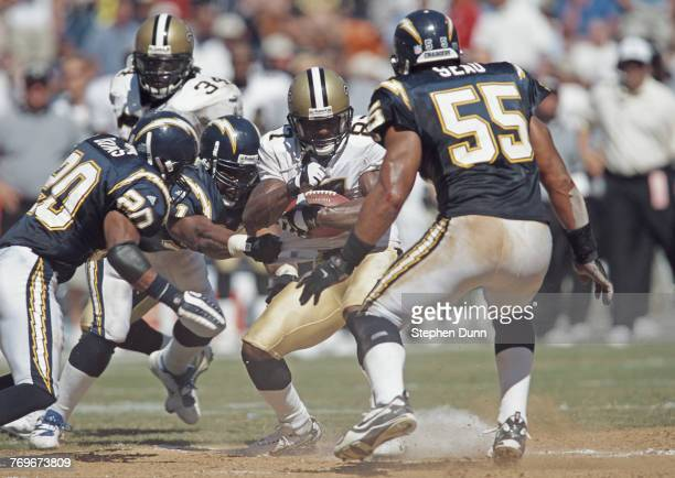 Joe Horn Wide Receiver for the New Orleans Saints is tackled by Gerald Dixon Mike Dumas and Junior Seau of the San Diego Chargers during their...