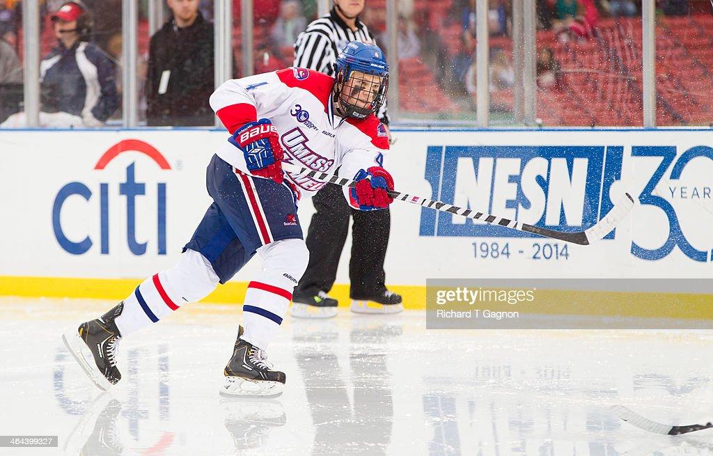 Joe Houk #4 of the Massachusetts Lowell River Hawks shoots the puck during NCAA hockey action against the Northeastern University Huskies in the 'Citi Frozen Fenway 2014' at Fenway Park on January 11, 2014 in Boston, Massachusetts.