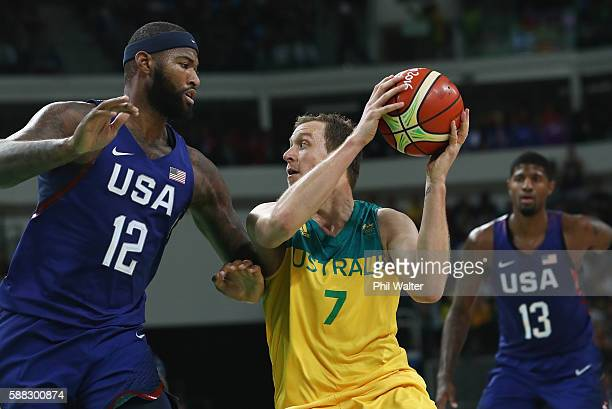Joe Ingles of Australia handles the bal against Demarcus Cousins of United States as Paul George looks on during the Men's Preliminary Round Group A...