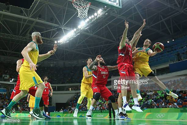 Joe Ingles of Australia makes a leaping pass around Milan Macvan of Serbia during the Men's Semifinal match on Day 14 of the Rio 2016 Olympic Games...