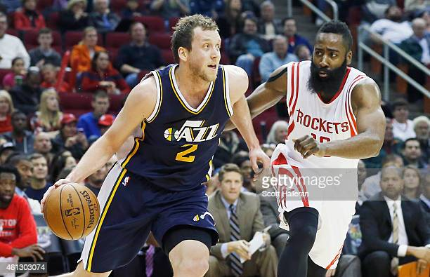 Joe Ingles of the Utah Jazz drives with the basketball in front of James Harden of the Houston Rockets during their game at the Toyota Center on...