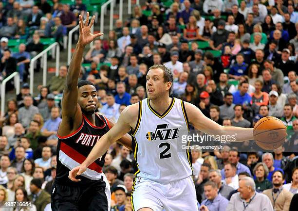 Joe Ingles of the Utah Jazz looks to pass around Maurice Harkless of the Portland Trail Blazers in the first half at Vivint Smart Home Arena on...