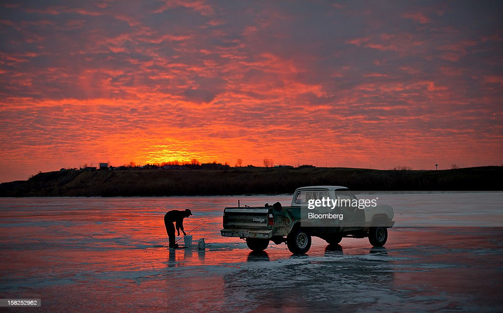 'BEST PHOTOS OF 2012' (): Joe Jessop, a truck driver from Orderville, Utah, sets his pole as while fishing on the frozen Missouri River in Williston, North Dakota, U.S., on Sunday, Feb. 12, 2012. North Dakota will hold its Republican presidential caucus on March 6. Photographer: Daniel Acker/Bloomberg via Getty Images