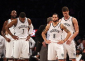 Joe Johnson Deron Williams and Brook Lopez of the Brooklyn Nets wait for a refs call in the closing minutes of their loss to the Chicago Bulls during...