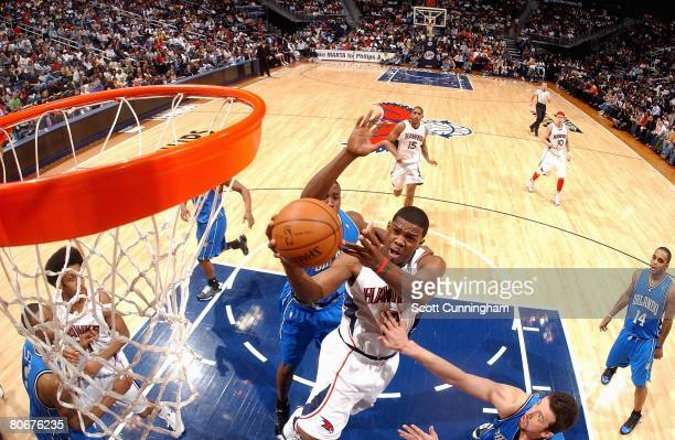 Joe Johnson of the Atlanta Hawks lays the ball up over Dwight Howard and Hedo Turkoglu of the Orlando Magic during the game on March 22 2008 at...