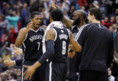 Joe Johnson of the Brooklyn Nets celebrates with teammates after hitting the game winning shot in double overtime to give the Nets a 115113 win over...