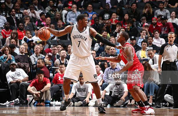 Joe Johnson of the Brooklyn Nets dribbles against Isaiah Canaan of the Houston Rockets during a game at the Barclays Center on April 01 2014 in the...