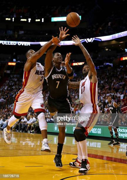 Joe Johnson of the Brooklyn Nets drives against Dwyane Wade and Udonis Haslem of the Miami Heat during a game at AmericanAirlines Arena on November 7...