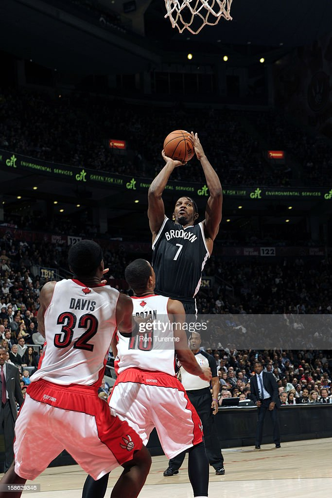 Joe Johnson #7 of the Brooklyn Nets shoots against DeMar DeRozan #10 and Ed Davis #32 of the Toronto Raptors on December 12, 2012 at the Air Canada Centre in Toronto, Ontario, Canada.