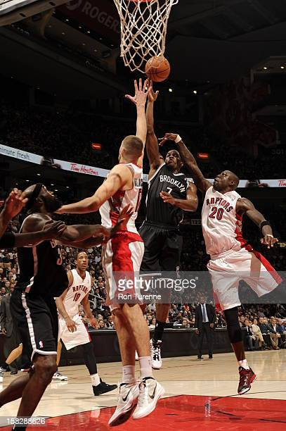 Joe Johnson of the Brooklyn Nets shoots the ball against Mickael Pietrus and Jonas Valanciunas of the Toronto Raptors on December 12 2012 at the Air...