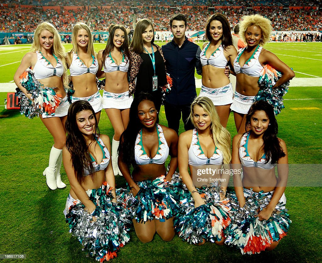 Joe Jonas of the Jonas Brothers poses for a photograph with the Miami Dolphins cheerleaders during a game against the Cincinnati Bengals at Sun Life Stadium on October 31, 2013 in Miami Gardens, Florida.