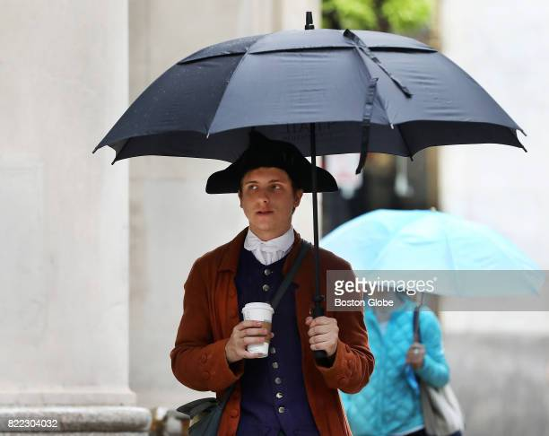 Joe Juknievich keeps his 18th century late Colonial costume dry in the rain on School Street near Downtown Crossing in Boston on Jul 24 2017 The...