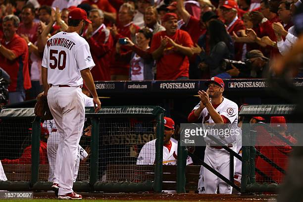 Joe Kelly celebrates with Adam Wainwright of the St Louis Cardinals as he returns to the dugout during Game Five of the National League Division...