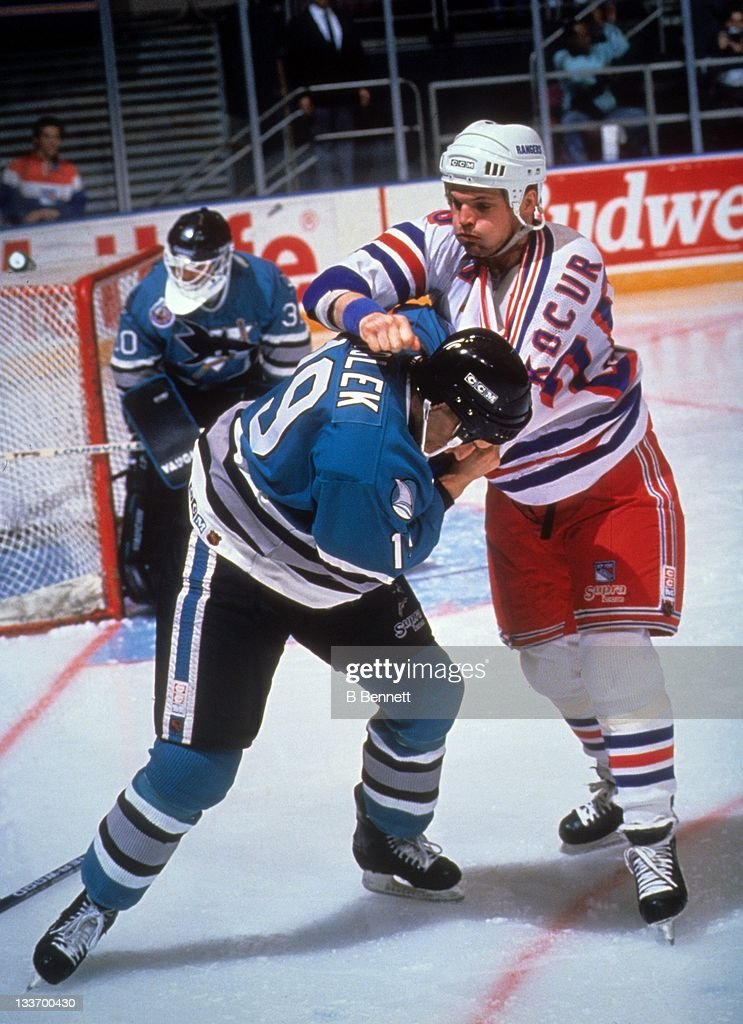Joe Kocur of the New York Rangers fights with Doug Zmolek of the San Jose Sharks during their game circa 1993 at the Madison Square Garden in New...