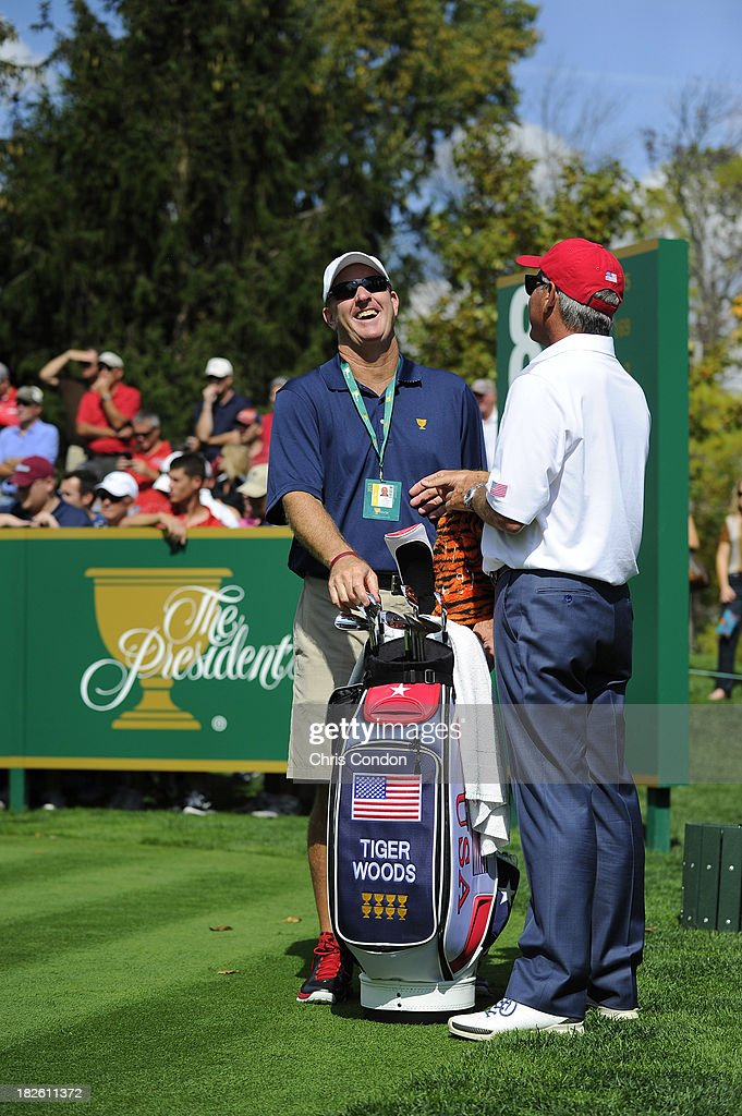 Joe LaCava, caddie for Tiger Woods of the U.S. Team shares a laugh with Fred Couples on the eigth hole during a practice round prior to the start of The Presidents Cup at the Muirfield Village Golf Club on October 1, 2013 in Dublin, Ohio.